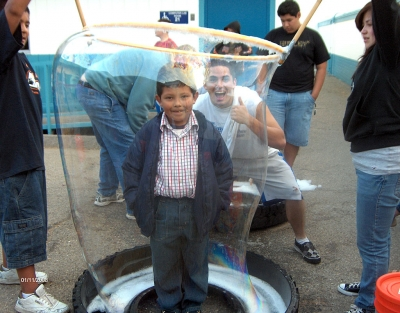 High School community service helper Christian Prado with 1st grader Carlos Rivas. It took them a few times to get Carlos with a full bubble around him.