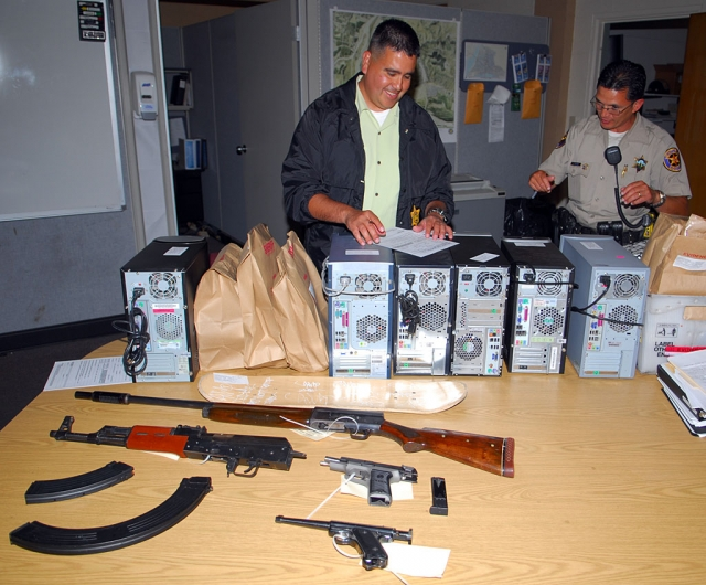 Fillmore Police Tagging Investigator Gene Torres, left, inspects the guns, ammunition, computers and other stolen property confi scated during a recent search warrant and probation searches at 7 city locations. Deputy Torres directed a 50-offi cer task force comprised of Fillmore Police and Ventura County Sheriff Deputies. Computers and cell phones taken from the residents of the arrestees will be searched for additional information.
