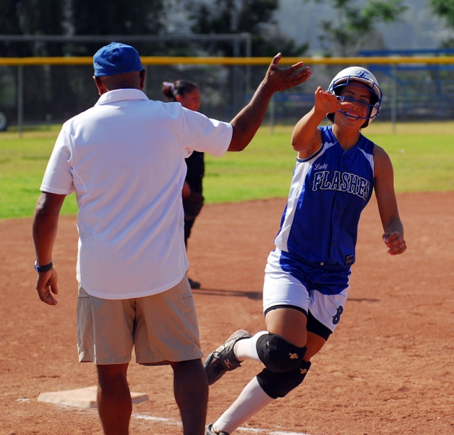 Nadia Lomeli high fives Coach Ortiz rounding third base. Lomeli hit a homerun over the center field fence and scored 3 runs.