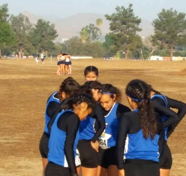 Fillmore Flashes girls cross country team huddle together before their race begins.