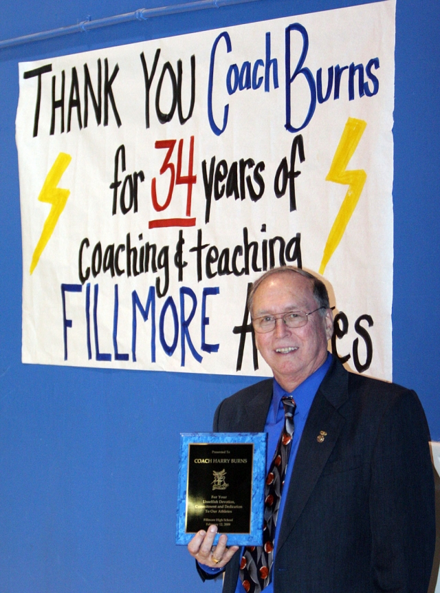 "After 34 years of teaching and coaching, Coach Harry Burns will be retireing this year. He will be missed by all students and staff. As the sign says ""Thank You Coach Burns."""