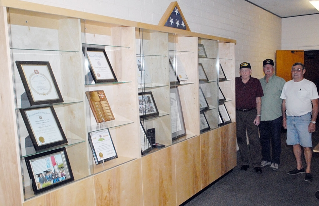 The Fillmore-Piru Veterans Memorial Building has just been enhanced by the addition of a cabinet for housing Veterans of Foreign Wars (VFW) awards and mementos. Shown here are VFW leaders John Pressey, Vic Westerberg, and Jim Rogers who have just filled the shelves with historical materials.