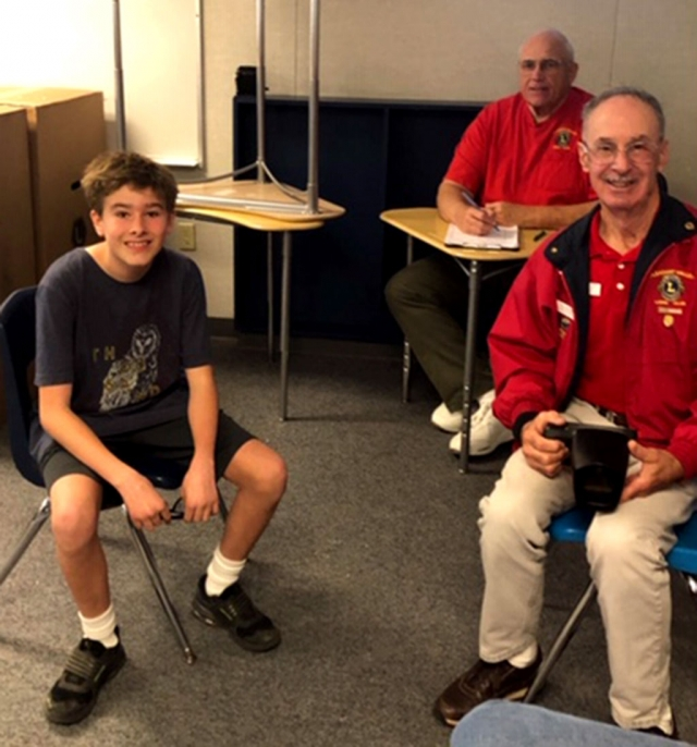 Pictured is Fillmore Middle School eighth grade student Cody Spore ready for his vision screening, while members of the Lions Club look on.