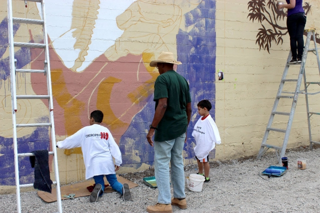 "(left) Cuban sculptor and painter Pedro Pulido mentoring kids while painting the ""Havana to Ventura"" Mural"