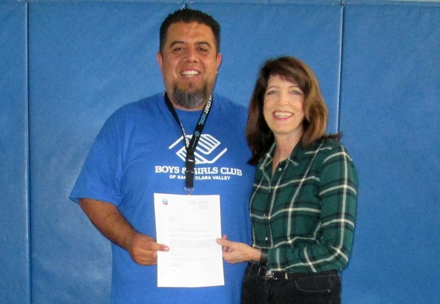 (left) Buddy Escoto, Site Director for the Fillmore Site of the Boys & Girls Club of Santa Clara Valley receiving a check for $5000 from Leslie Klinchuch, Project Manager for Chevron. The funds will be used to continue the high quality STEM (Science, technology, engineering and math) programs being implemented at the Club. Thank you Chevron!
