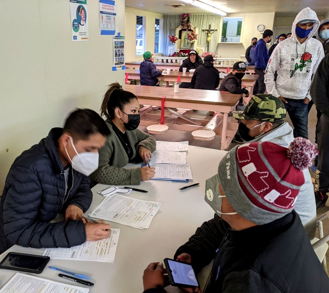 Volunteers helping farmworkers register to get their COVID-19 vaccines.