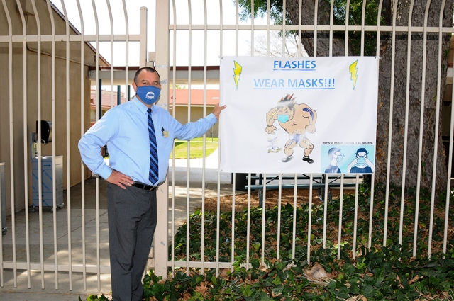 FHS Principal John Wilber standing next to a sign reminding students and staff to wear their masks.