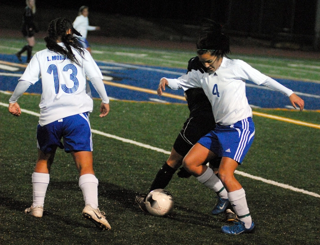 Princess Vaca #4 fights for the ball against Oak Park, her teammate Luz Morenes come to assist.