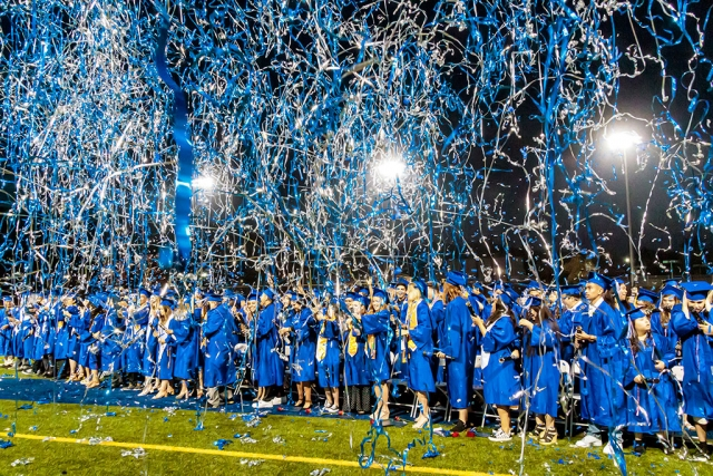 "Photo of the Week: ""Tassels crossed to other side of the mortarboard (caps), graduates celebrate by firing blue & white streamers into the air"" by Bob Crum. Photo info: Canon 7DMKII camera, manual mode, Tamron 16-300mm lens @16mm. Exposure; ISO 10000, aperture f/10, 1/125th of a second shutter speed."