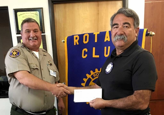 Police Chief Dave Wareham, left, presents Fillmore Fire Chief Keith Gurrola with a donation check for $500 from the Fillmore Rotary Club to go towards books for the Community Give Away which will take place December 16th.