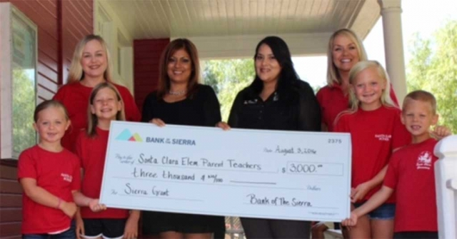 Jennie Andrade, Assistant Vice President, Fillmore Branch, and Adriana Mejia, the Financial Service Representative of the Fillmore Branch presented the check to Kari Skidmore, Principal and Amber McCalister, PTO President and some of the school's children in front of Santa Clara Elementary School.