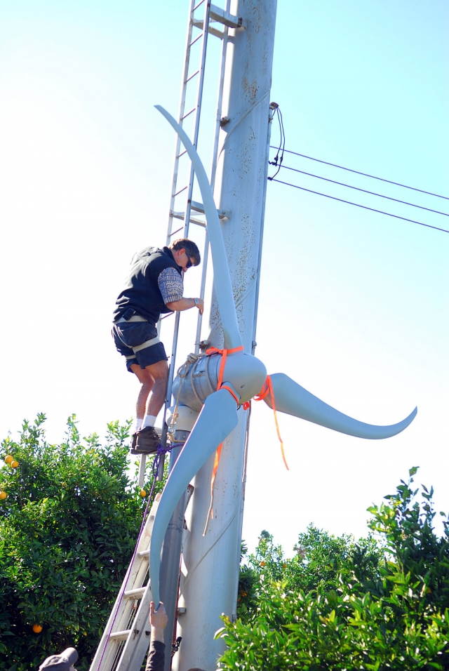 Installation of a new wind generator takes place under the watchful eyes of local farmer Bob Hammond. Converting his old orchard wind machine is expected to produce up to 500 kilowatts per month for the Hammond household. This is about as green as it gets.