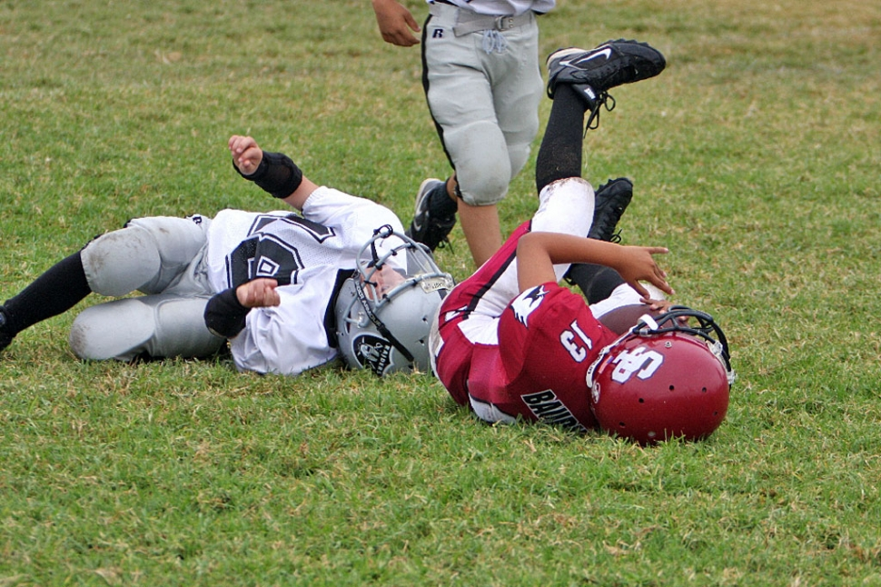 An Unidentified Raider Defender takes down a Cardinal Ball carrier