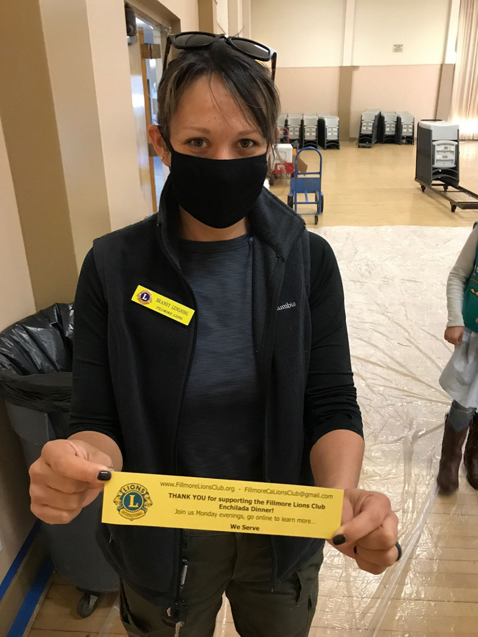Lion Club member Brandy Lengning holding up a thank you slip.